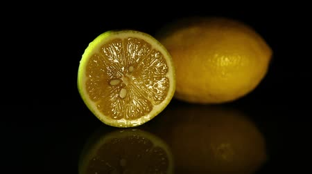 cítrico : A slice of lemon and a whole juicy lemon on a dark mirror table. HD