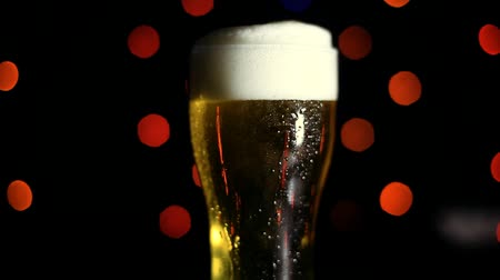 пивоваренный завод : A glass of cold beer on a black background with colored lights. Drops of water flow down the glass. Стоковые видеозаписи