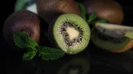 yarım uzunluk : Fruits of juicy kiwi rotate on a table on a black background. HD. Close-up
