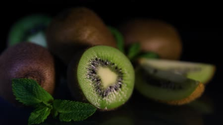 yarım uzunluk : Fruits of juicy beautiful kiwi lie on a table on a black background. Close-up.