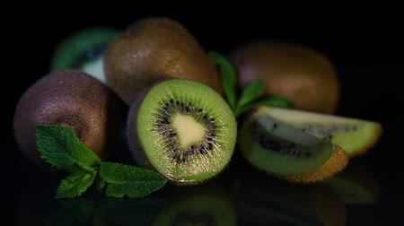 kivi : Delicious beautiful fruit kiwi and mint lie on a black table Stok Video