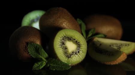 healthyfood : Delicious juicy fruit kiwi and mint lie on a black table. Reflection of kiwi from the table. HD. Close-up