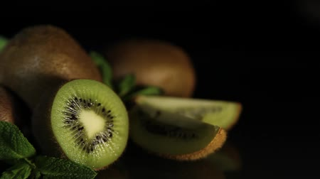 kivi : Delicious juicy fruit kiwi and mint lie on a black table. Reflection of kiwi from the table. HD.