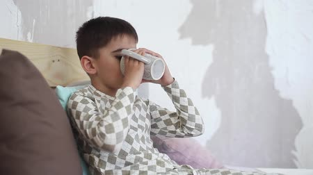 nepořádek : Little boy drinks tea from mug sitting on bed.HD
