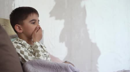 tecido : A little boy coughs for a cold and takes cover with a blanket Stock Footage