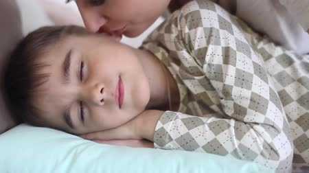 bochecha : Mom kisses the little son while he is sleeping. The son wakes up having a good mood