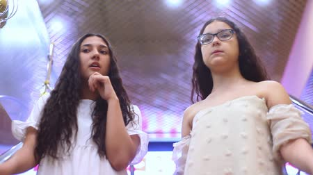 pitka : Two beautiful cheerful girls go down the escalator during shopping and discuss shopping in the mall with a good mood. HD. Close-up