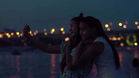 fad : two girlfriends do selfie on a background of a night city. slow motion