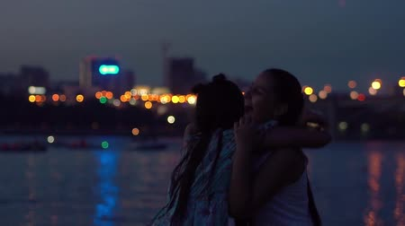 fad : two girlfriends embrace on a background of a night city. slow motion