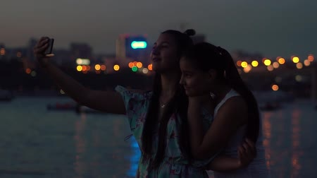 taco : two girlfriends do selfie at night on a background of lights. slow motion