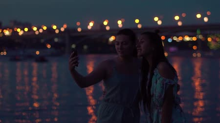 fad : two girlfriends do selfie at night by the river against the backdrop of lights. slow motion