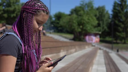 ebook : A girl uses a tablet while sitting on a park bench Stock Footage