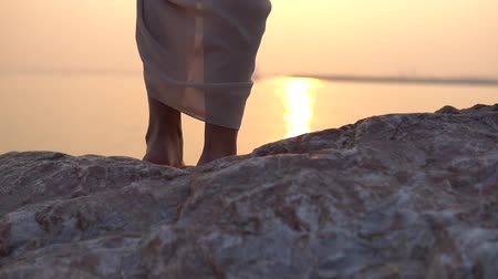 passo : Close-up. The dress is developed in the wind against the background of sunset. slow motion