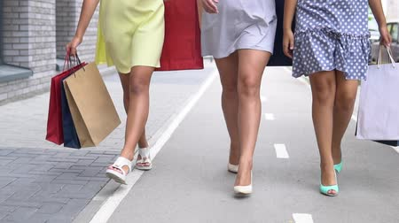 rua : Three beautiful girlfriends go along the street with packages after shopping and talk with each other. slow motion. Vídeos