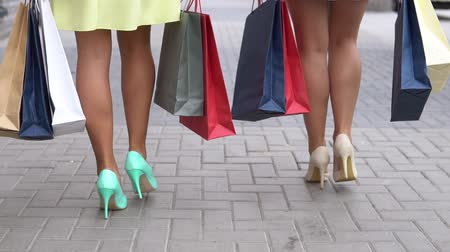 vysoký : Two girlfriends carry packages of different colors with shopping after shopping walking down the street. slow motion. HD