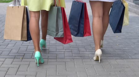 clipe de papel : Two girlfriends carry packages of different colors with shopping after shopping walking down the street. slow motion.