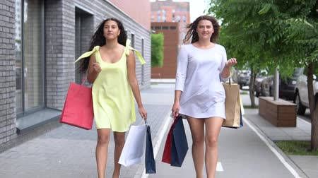 каблуки : Two beautiful girlfriends carry packages of different colors with shopping after shopping. slow motion. HD