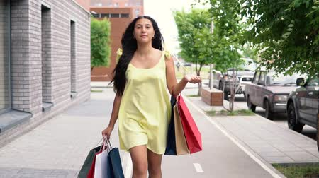 pitka : A beautiful girl in a yellow dress is walking down the street after shopping having a good mood. slow motion.