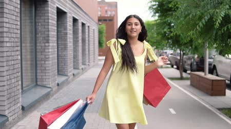 pitka : An attractive young girl with dark hair in a yellow dress rejoices after shopping with a good mood. slow motion.