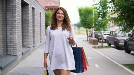 три человека : A girl in a light dress is walking down the street after shopping. slow motion.