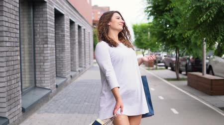 consumerism : A girl in a light dress goes down the street after shopping and carries packages with purchases in her hands. slow motion. Stock Footage