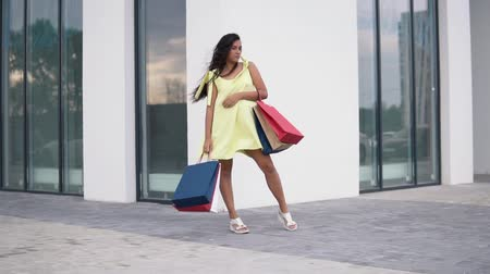 move well : Beautiful girl model after shopping with colored bags in hands. slow motion.