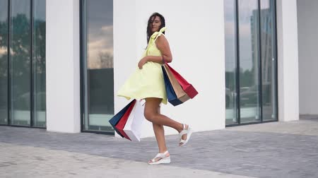 скидка : Beautiful girl model in a long dress after shopping with colored bags in hands. slow motion.