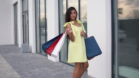 move well : Beautiful girl model in a long dress after shopping with colored bags in hands having a good mood. slow motion.