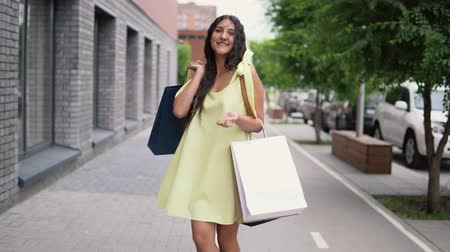 потребитель : Young girl in a long dress after shopping with a good mood.