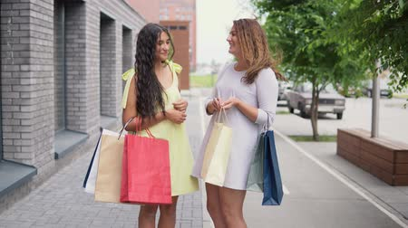move well : Two attractive girlfriends discuss buying after shopping. 4K.