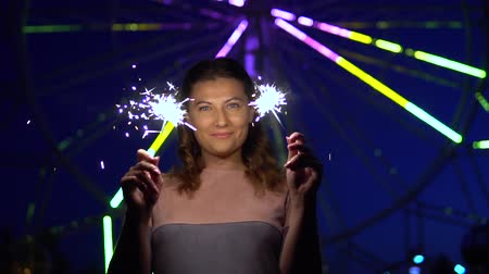 bochechudo : An attractive girl is happy with a holiday with fireworks in her hands. slow motion. Vídeos