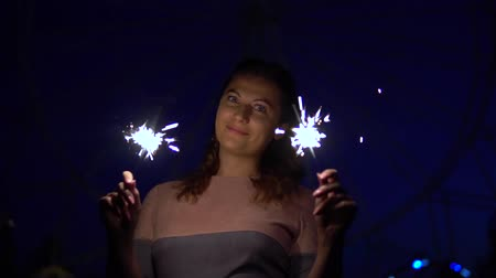 mischief : An attractive young girl enjoys a holiday with fireworks in her hands having a good mood. slow motion. HD Stock Footage