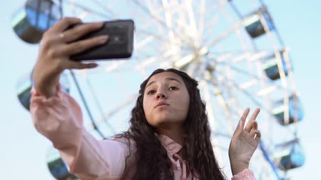 mobile music : a girl with long hair in a dress makes selfie using a phone standing near the Ferris wheel. slow motion. Portrait Stock Footage