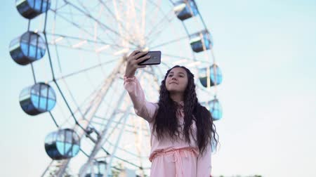 tło retro : a girl with long hair in a dress makes selfie using a smartphone standing near the Ferris wheel. slow motion.