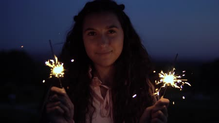 csillagszóró : Young girl with fireworks in hands on a background of a night city. slow motion.