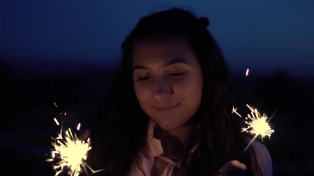 канун : A young girl with long hair stands with fireworks in her hands against the background of a night city. slow motion. Portrait Стоковые видеозаписи