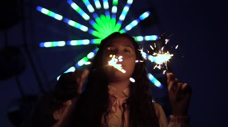 kutluyor : A young girl with long dark hair stands against the background of the city at night and holds fireworks in her hands. slow motion. HD Stok Video