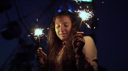 bengálsko : A young girl with long dark hair stands against the background of the city at night and holds fireworks in a good mood. slow motion. HD