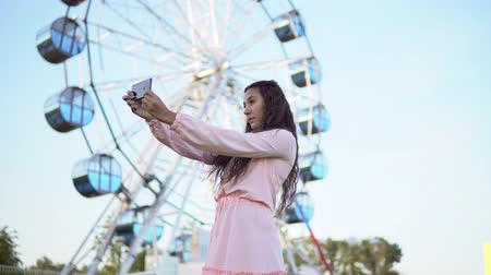 elküldés : a girl with long hair in a pink long dress makes selfie using a smartphone while standing near the Ferris wheel. 4K