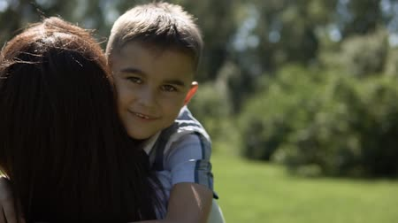 smutek : A small son runs to his mother in his arms and hugs her. slow motion. Close-up Wideo