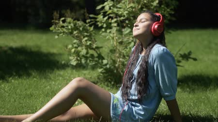 шмель : Young girl with long dark hair listening to music on headphones using a tablet sitting on grass in a park having a good mood.slow motion. HD Стоковые видеозаписи