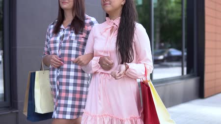 bolsa de compras : Two young girls go after shopping holding shopping bags. slow motion. Stock Footage