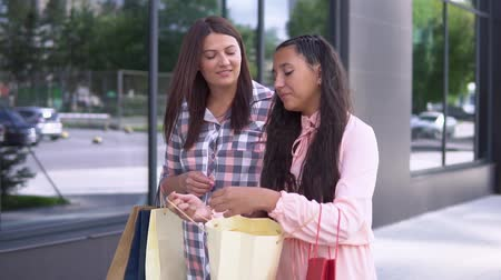pitka : Two attractive girls in beautiful dresses go after shopping near the mall holding shopping bags. slow motion.