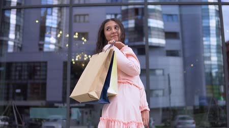 тек : Young girl in a dress after shopping with bags in hands. 4K Стоковые видеозаписи