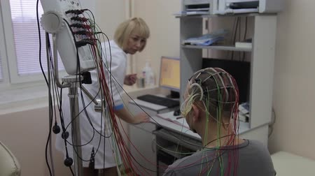 функция : A male patient is sitting on a chair. To his head and hands are connected medical devices and sensors for health research. Progress in medicine. Cyber Technology.4K Стоковые видеозаписи