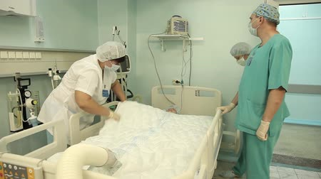 acil : A group of doctors connect the device to heat the patient after the operation. Stok Video