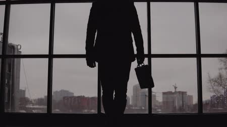 move well : businessman with a case in hand goes to the window in the office and looks at the city Stock Footage