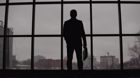 arka görünüm : businessman stands at the window in the office and looks at the city. 4K Stok Video