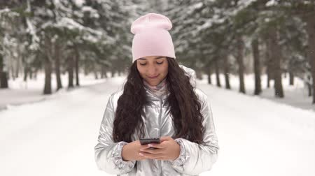 jel : Attractive girl walks through the winter forest and uses a smartphone. 4K