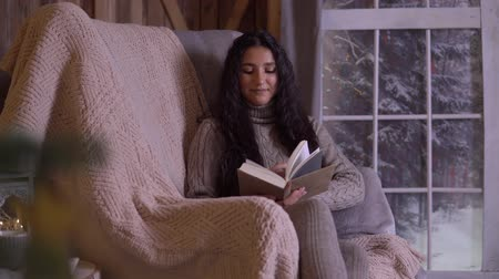 knitted : A young girl is reading a book while sitting in a chair near the Christmas tree.